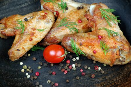 Chicken baked wings on wooden background. chicken wings, tomatoes and pepper mix, close-up