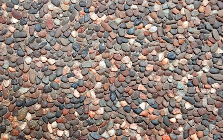 Pebble texture background. Colorful pebble stone texture on the road. Pavement of small stones