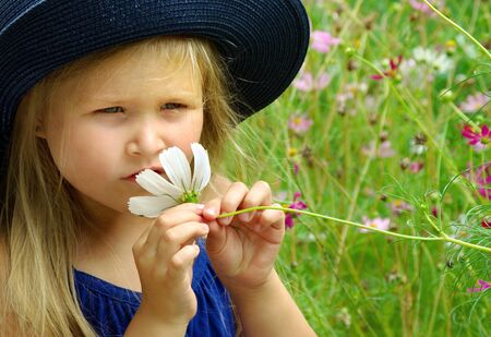child sniffing flower. girl with a flower in her hand. child among the flowers.