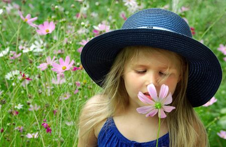 child sniffing flower. girl with a flower in her hand. child among the flowers. pollen allergy 版權商用圖片