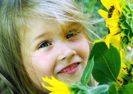 little girl in a wreath. child among the flowers. girl with sunflower