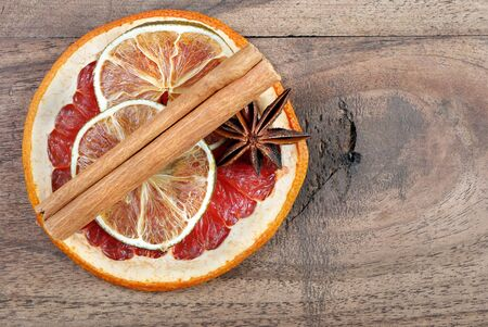 dried fruits and spices on a wooden table. Christmas background. slices of dry lime, grapefruit, anise stars and cinnamon sticks. top view