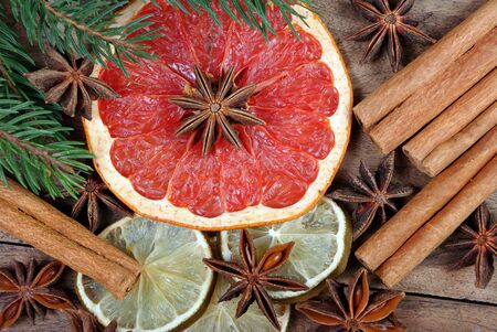 dried fruits and spices on a wooden table. Christmas background. slices of dry lime, grapefruit, anise stars and cinnamon sticks.