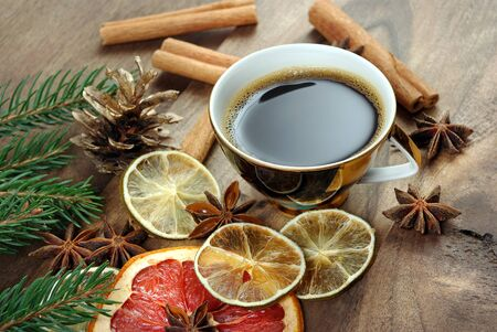 Christmas background. dried lemon, grapefruit, anise stars, cinnamon, cup of coffee and christmas tree branches on a wooden table. cup of coffee, spices and dried fruits. copy spaces Reklamní fotografie