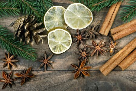 Christmas background. dried lemon, anise stars, cinnamon, and christmas tree branches on a wooden table. spices and dried fruits.