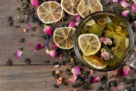 tea with lemon. cup of tea and dried lemons on a wooden table. green tea with dried flowers roses top view