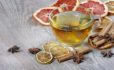 cup of herbal tea with lemon, dried citruses, anise stars and cinnamon sticks on a wooden table. hot tea for colds and flu