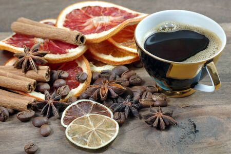 Christmas background. dried lemon, orange, grapefruit, anise stars, cinnamon, cup of coffee and roasted coffee beans on a wooden table. cup of coffee, spices and dried fruits.