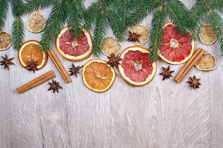 Christmas background. Christmas tree branches, dried citruses, cinnamon sticks and anise stars on a wooden table. mulled wine ingredients and spices. copy spaces
