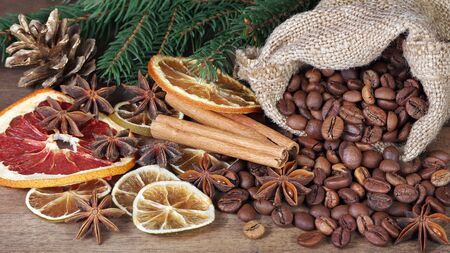 Christmas background. roasted coffee beans in a sack, dried citruses and spices on a wooden table. Reklamní fotografie