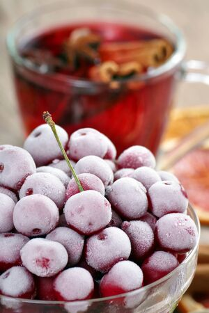 frozen cherry in a glass bowl and cup of mulled wine. frozen berries close-up. cold and flu remedy Reklamní fotografie