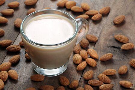 Latte di mandorle in una tazza di vetro su un tavolo di legno. mandorle e latte.