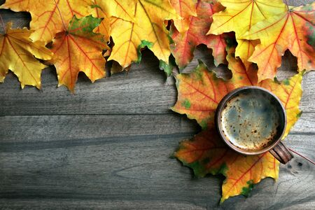 autumn drink concept. cup of coffee and autumn maple leaves on a wooden table. top view. copy spaces. Reklamní fotografie
