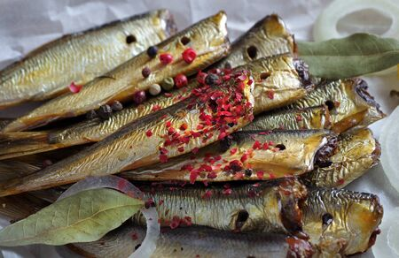 smoked fish and spices close-up. smoked sprats in pink and black pepper