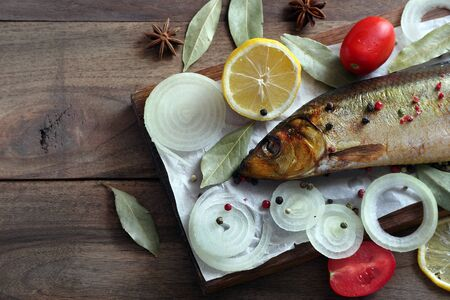 smoked fish and spices on a wooden table. smoked herring on a cutting board. top view. Reklamní fotografie