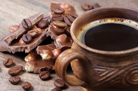 cup of coffee and chocolate. milk chocolate with hazelnuts and black coffee on a wooden table.