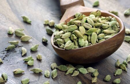 green cardamom pods in a wooden spoon on a wooden table