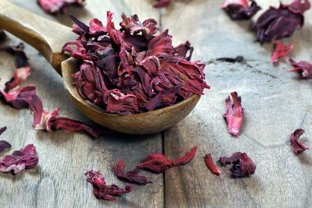 dry hibiscus in a wooden spoon. dried hibiscus petals on a wooden table. hibiscus tea. vitamin tea for cold and flu.