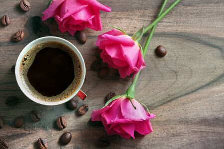 cup of coffee and roses on a wooden table. copy spaces. top view
