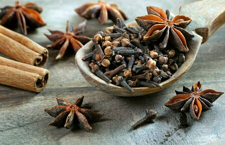 Christmas spices for mulled wine. cloves in a wooden spoon. traditional spices. dry cloves, anise stars, cinnamon and cardamom on a wooden table.