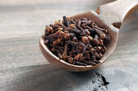 cloves in a wooden spoon. traditional spices.