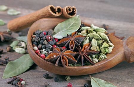traditional spices. dry cloves, anise stars, cardamom, cinnamon, mixture of peppers and bay leaf in a wooden spoon.