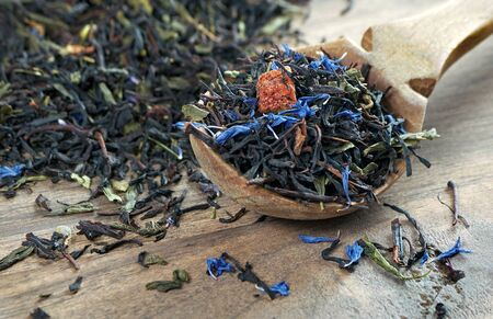 blended tea. black tea with dry flower petals and fruits. dry black tea leaves in a wooden spoon. close up Stock fotó