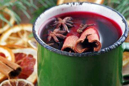 Christmas background. mulled wine in a vintage green mug. mulled wine with traditional spices and dried citruses. cold and flu remedy.