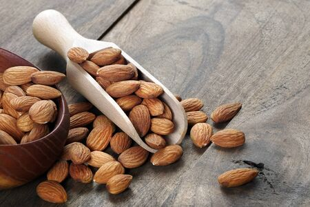 almonds in a scoop on a wooden table.
