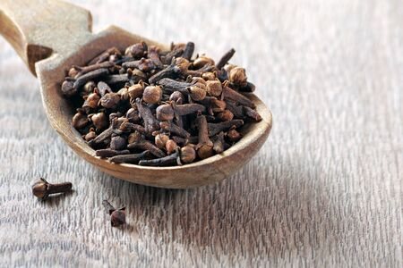 cloves in a wooden spoon. traditional spices. copy spaces
