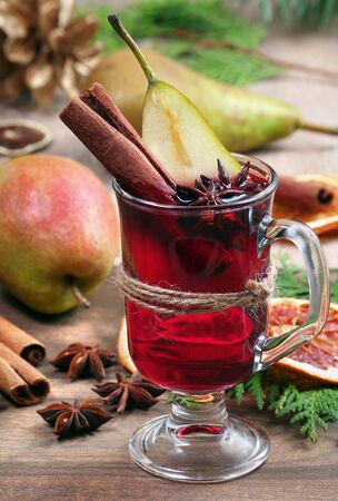 Christmas background. mulled wine and ripe pears. cup of mulled wine and traditional spices on a wooden table close-up Stock fotó