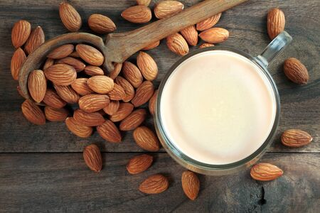 Almond milk in a glass cup on a wooden table. almonds and milk