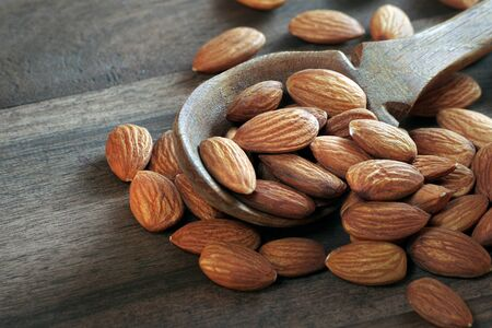 almonds in a wooden spoon on a wooden table
