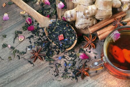 cup of fresh tea and spices. black blended tea, ginger, anise and cinnamon on a wooden table. tea in a wooden spoon and traditional spices Stock fotó