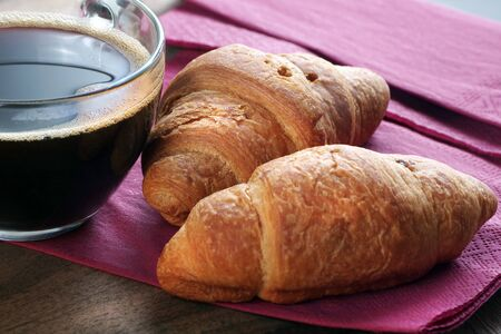 croissants and a cup of coffee on a wooden table. top view. copy spaces Stock fotó