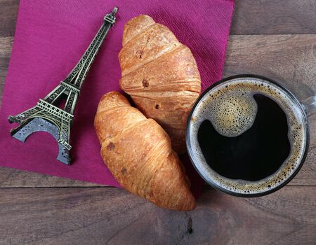croissant and Paris. croissants and eiffel tower as a souvenir. croissants and cup of coffee on a wooden table. top view. copy spaces