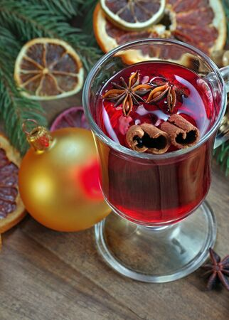 Golden Christmas ball, mulled wine and spices. Christmas background. mulled wine in a glass. mulled wine with traditional spices and dried citruses. cold and flu remedy.
