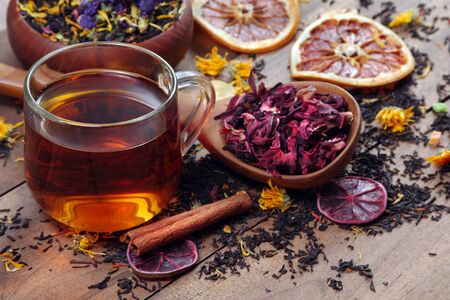 Assortment of dry tea. different varieties of tea on a wooden table. blended tea with flower petals, hibiscus in a wooden spoon and dried citruses.