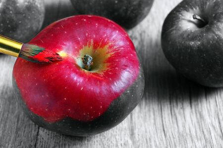 coloring this world. artist brush paints an apple. color and shape. red apple close-up.