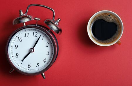 Good morning concept. Alarm clock on a red background and cup of coffee. Seven o'clock in the morning. top view