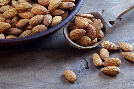 nuts. almonds in a spoon on a wooden table. close up