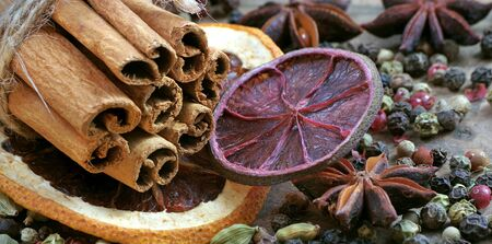 traditional spices for mulled wine. cinnamon sticks, anise stars, cardamom, pepper, and dry citruses on a wooden table.