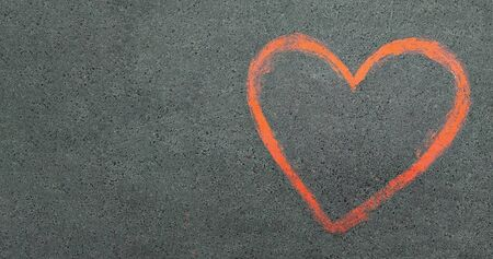 asphalt texture background. Red heart is a symbol of love drawn on the pavement. chalk drawings on asphalt. copy space