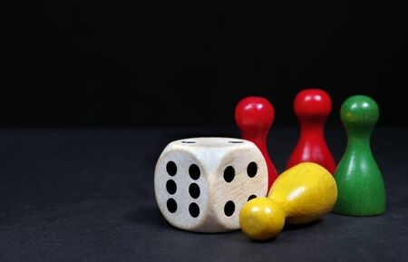 colorful play figures with dice on black board. selective focus