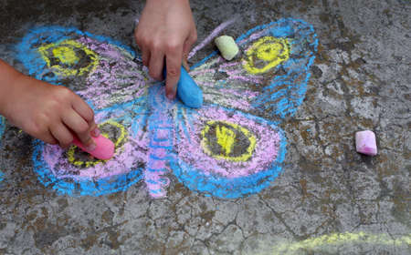 Children's drawings on the pavement. children draw butterflies with chalk on the pavement.