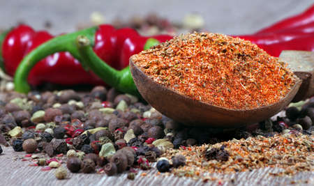 mixture of different peppers on a wooden table. traditional spices.