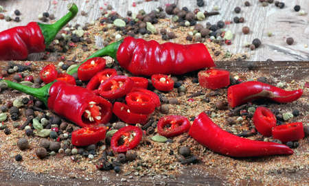 red hot chili peppers and a mixture of different peppers on a wooden table. traditional spices.