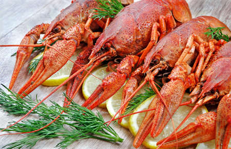 red boiled crayfish on a wooden table close-up.