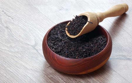 dry black tea leaves in a wooden bowl. black tea in a scoop