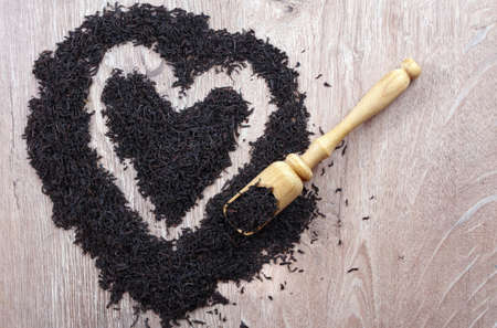 concept i love tea. dry black tea leaves on a wooden table. heart symbol made from black tea leaves. top view. copy space